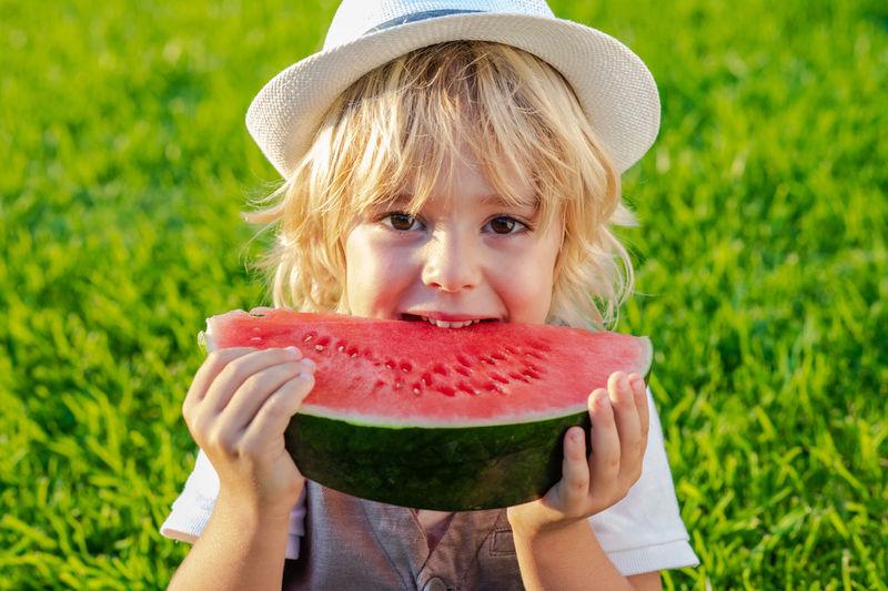 Boy holding watermelon on field