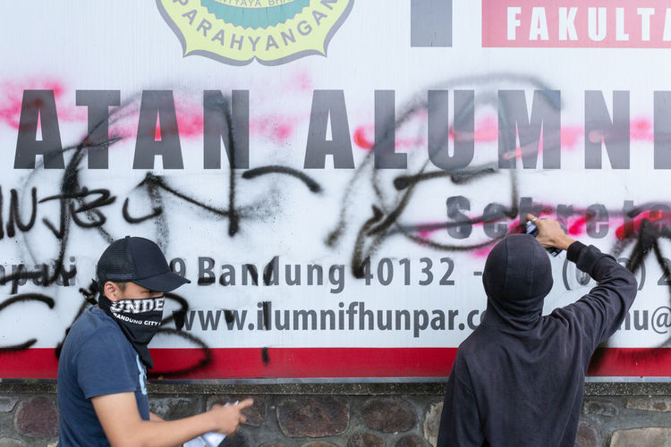 People standing against graffiti wall
