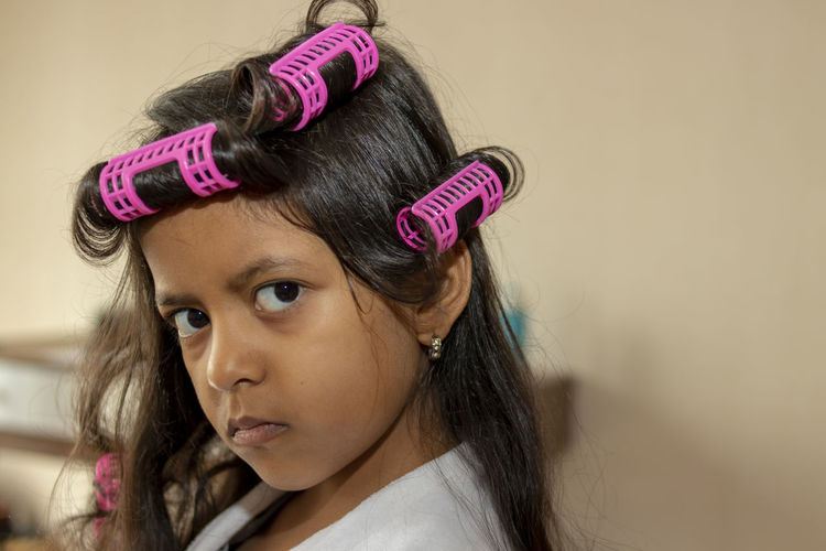 Close-Up Portrait Of Girl Wearing Hair Curlers At Home
