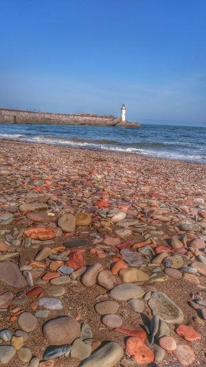 Water Sea Beach Tranquil Scene Beauty In Nature Clear Sky Coastline Beachphotography Lighthouse Tower Harbourview Stones And Pebbles Whitehaven Habour Colour Image Seascape Photography Seascapes