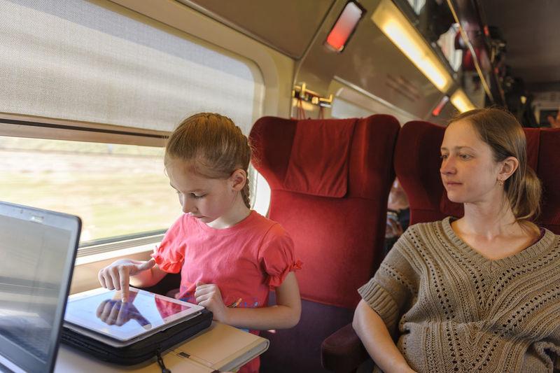 Woman looking at girl using digital tablet in train