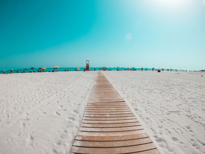 Boardwalk on beach against clear blue sky