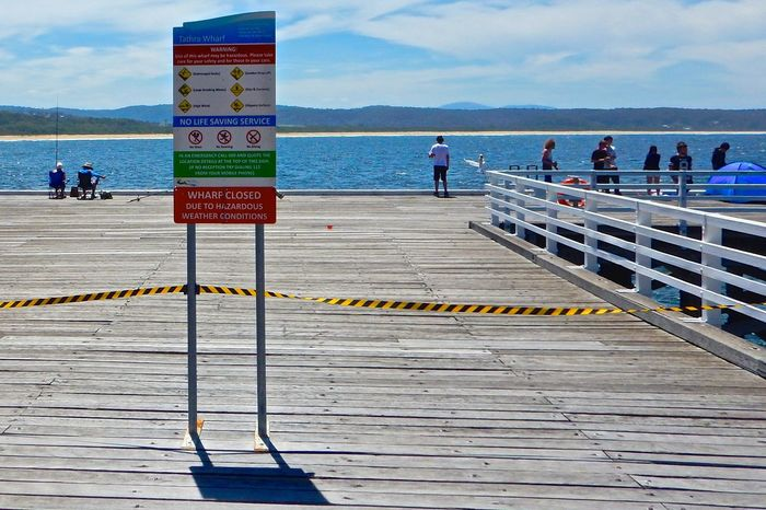 in Tathra, Australia. Barrier Boardwalk Cloud - Sky Day Fishing Fishing Time Group Of People Men Notice Notices Outdoors People Pier Real People Resist Resistance  Scenics Sea Sign Signage Signboard Sky Warning Sign Water Wharf