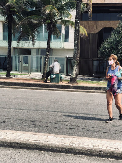 Full length of woman on footpath by palm trees