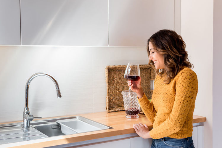 Full length of a woman drinking glass at home