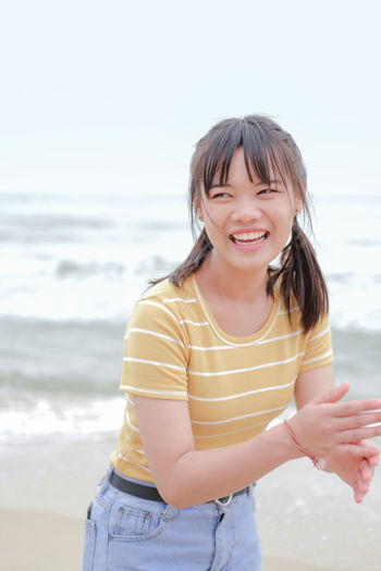 Portrait of smiling woman standing on beach