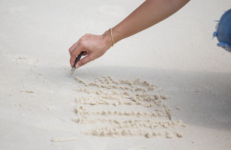 Close-up of woman drawing at beach with stick