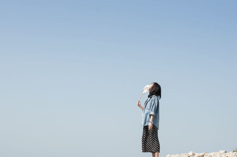 Woman holding folding fan looking up while standing against clear sky