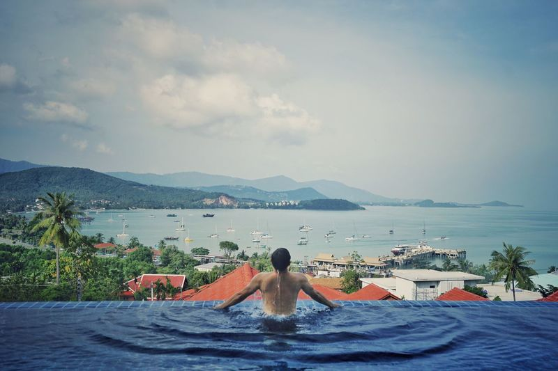 Rear View Of Shirtless Man In Infinity Pool Looking At Sea Against Sky