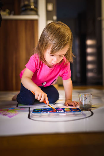 Child painting on the floor