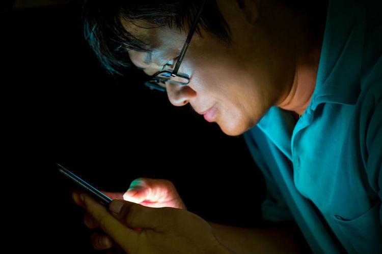 Close-up of man wearing eyeglasses using mobile phone