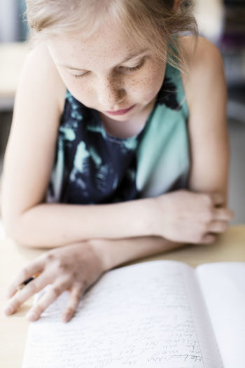 Close-up of girl sitting on book
