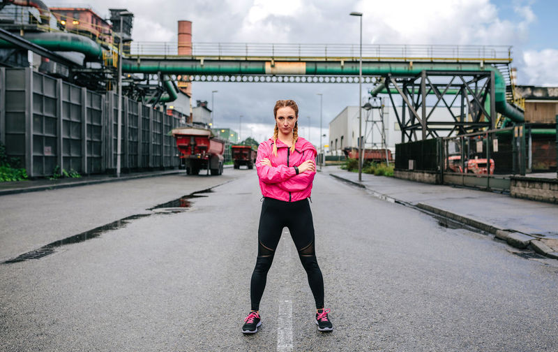 Full length portrait of woman standing on bridge