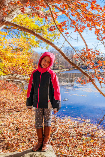 Portrait of girl wearing hooded jacket at lakeshore in forest during autumn