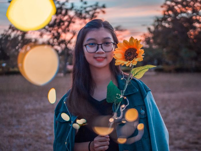 Portrait Of Smiling Young Woman Holding Sunflower With Illuminated String Lights During Sunset