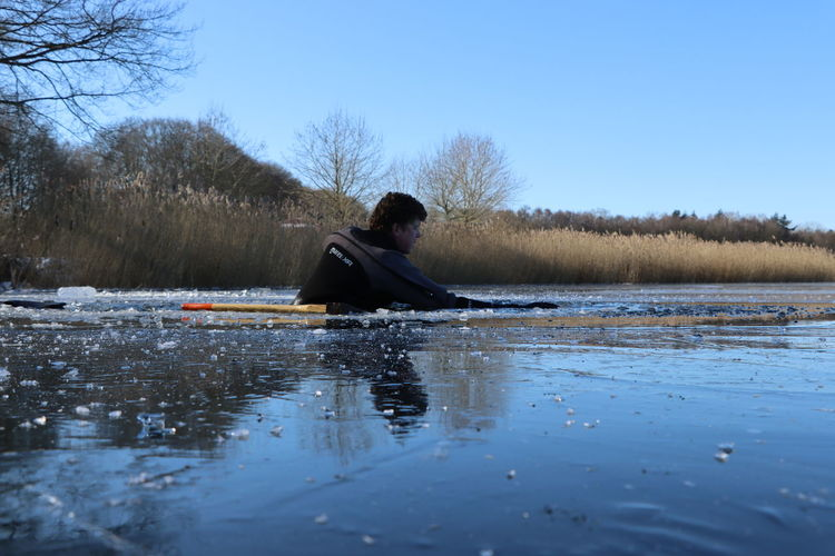Man sitting in lake against sky during winter