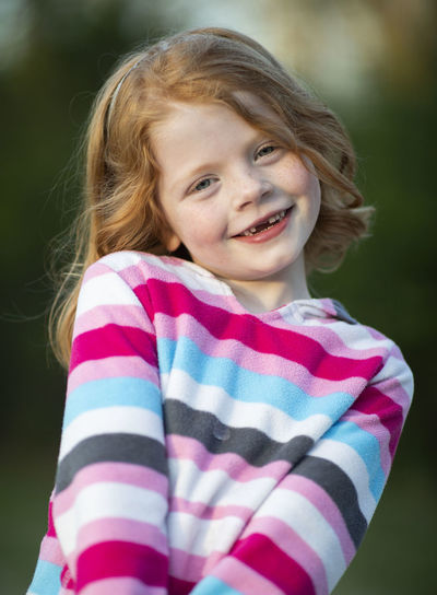 A five-year-old girl smiles for a candid portrait with shallow depth of field. Childhood Smiling Portrait Child Happiness Looking At Camera Striped Emotion Innocence Cheerful Girls Casual Clothing Women One Person Females Waist Up Front View Focus On Foreground Hair Hairstyle Outdoors Girl Red Hair Redhead Stripes Bokeh 85mm F1.4 Lens Smile Shallow Depth Of Field Dof DOF Portrait