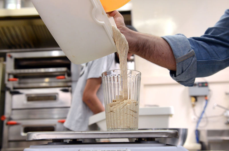 Cropped hand of man preparing food in commercial kitchen