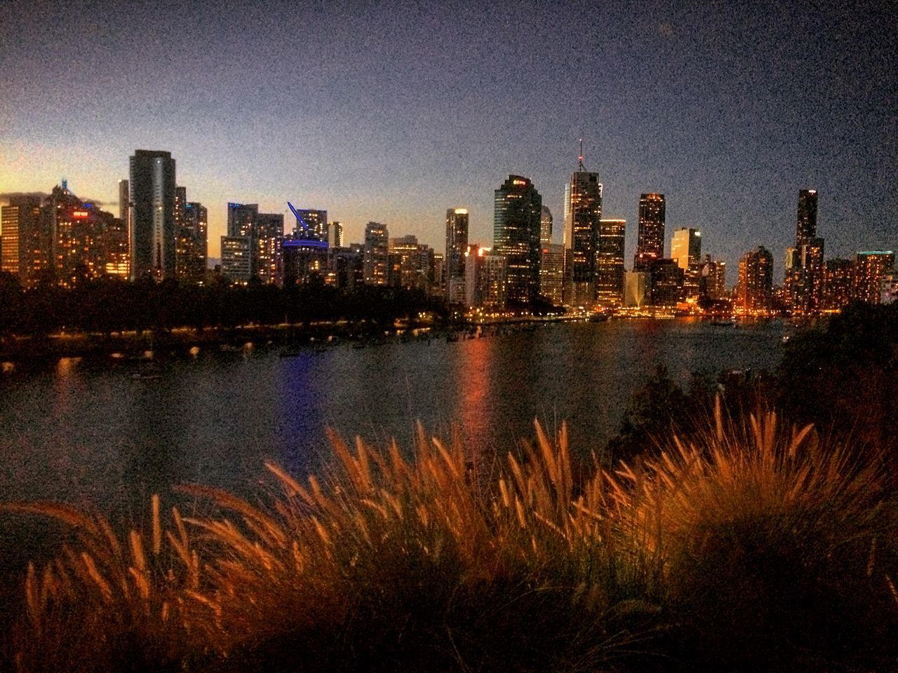 skyscraper, architecture, building exterior, cityscape, city, urban skyline, built structure, tower, travel destinations, skyline, modern, growth, no people, river, sky, tall, outdoors, illuminated, clear sky, night, water