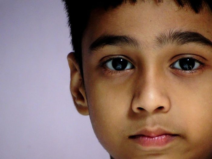 Close-up portrait of boy against purple background