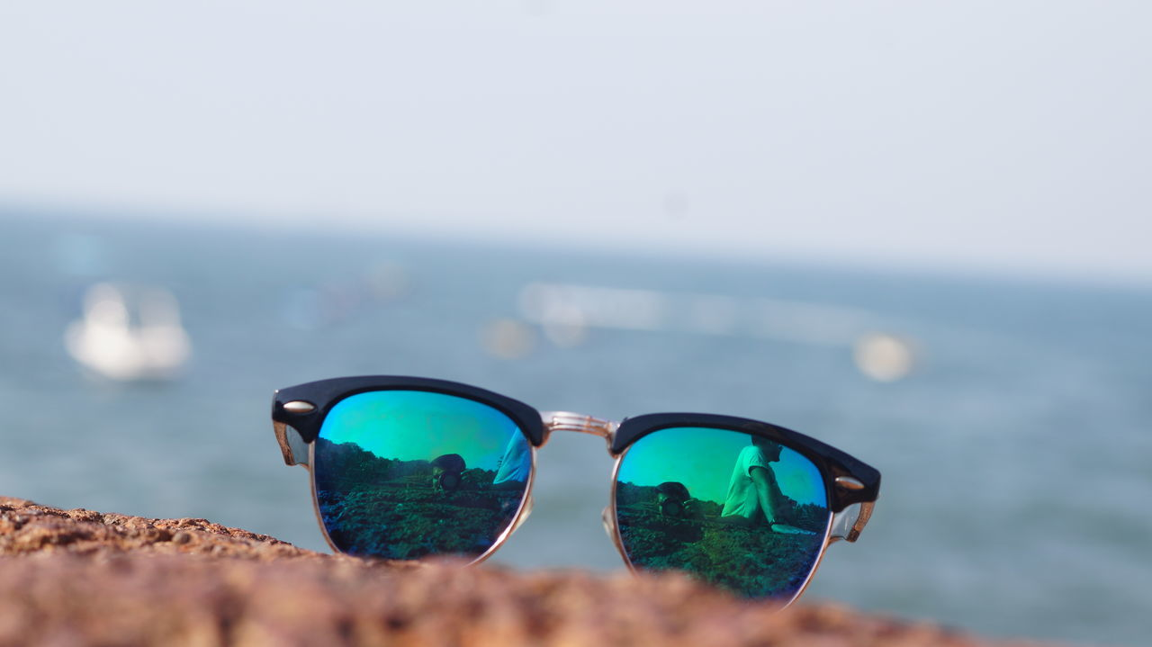 sunglasses, sea, water, horizon over water, no people, clear sky, nature, focus on foreground, sky, day, eyewear, eyeglasses, outdoors, beauty in nature, close-up, beach