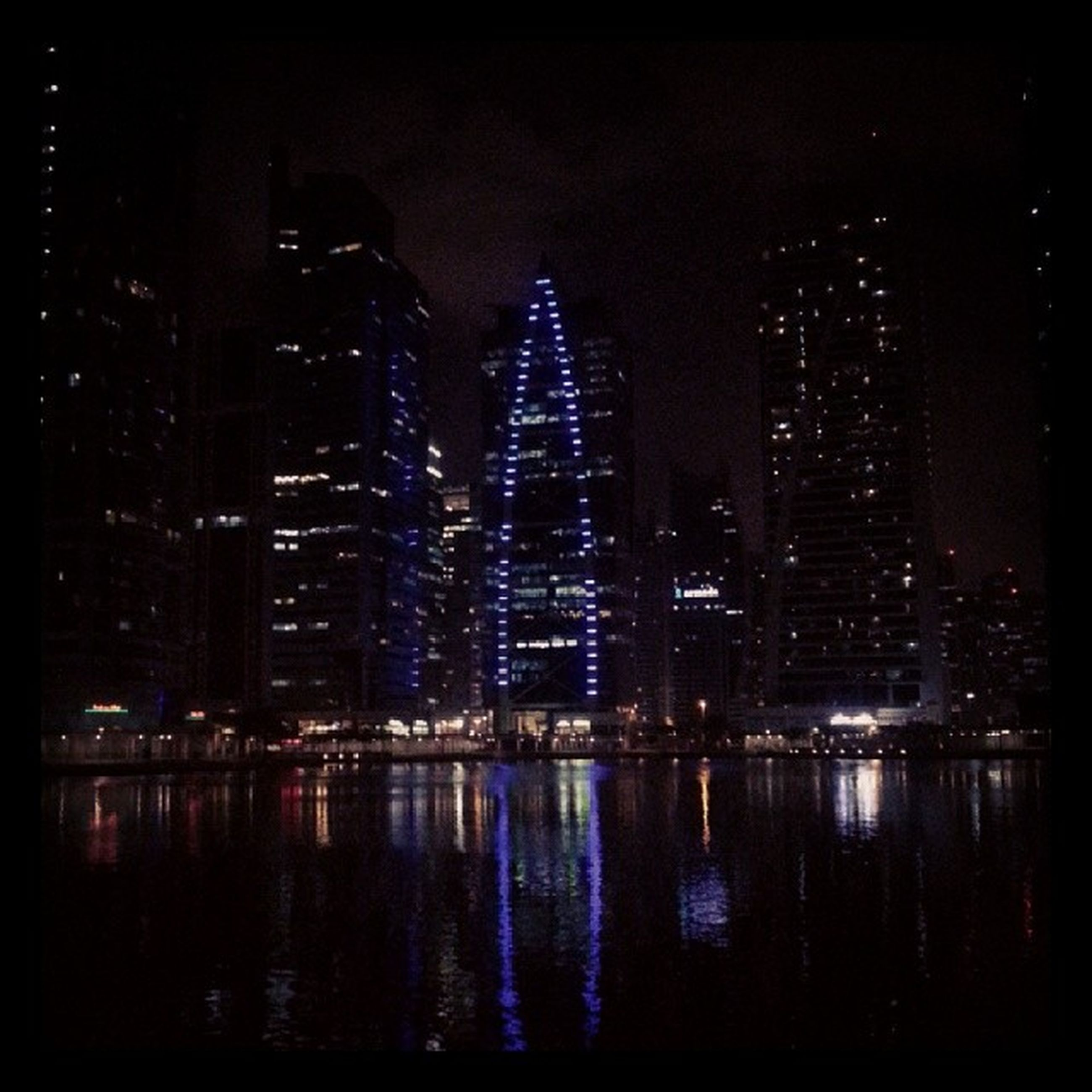 night, illuminated, building exterior, city, water, architecture, reflection, built structure, skyscraper, waterfront, cityscape, modern, river, office building, urban skyline, tall - high, tower, sky, building, financial district