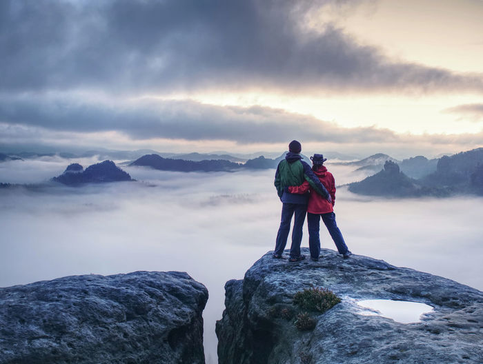 Lovely heterosexual couple looking at far sunrise in heavy clouds. dark night in foggy mountain ends