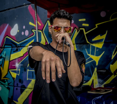 Hip Hop Medellín Art And Craft Casual Clothing Commune 13 Comuna 13 Creativity Front View Glasses Graffiti Holding Leisure Activity Lifestyles Mid Adult Mid Adult Men One Person Portrait Real People Standing Sunglasses Three Quarter Length Waist Up Young Adult Young Men