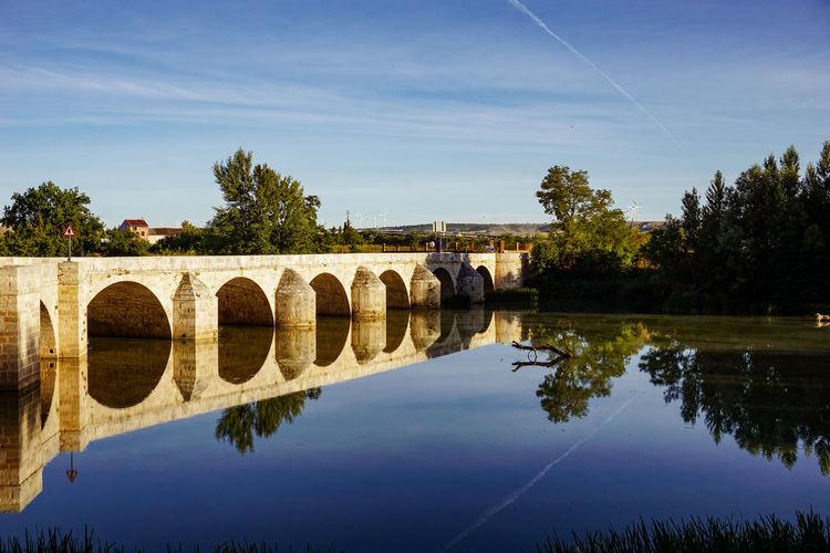 Arch bridge over river against sky
