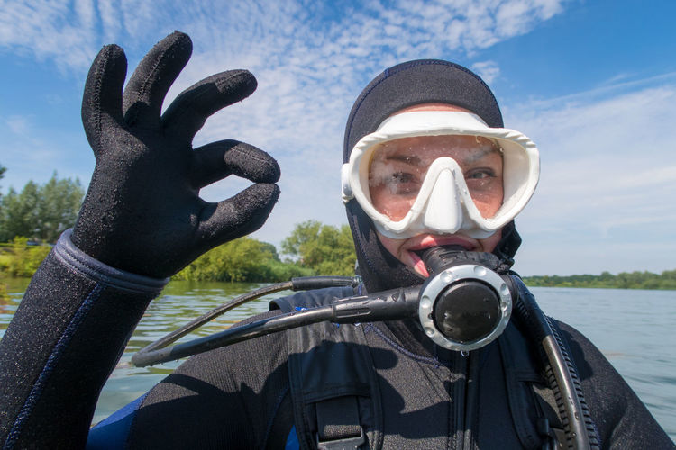 Close-up portrait of scuba diver showing ok sign against river