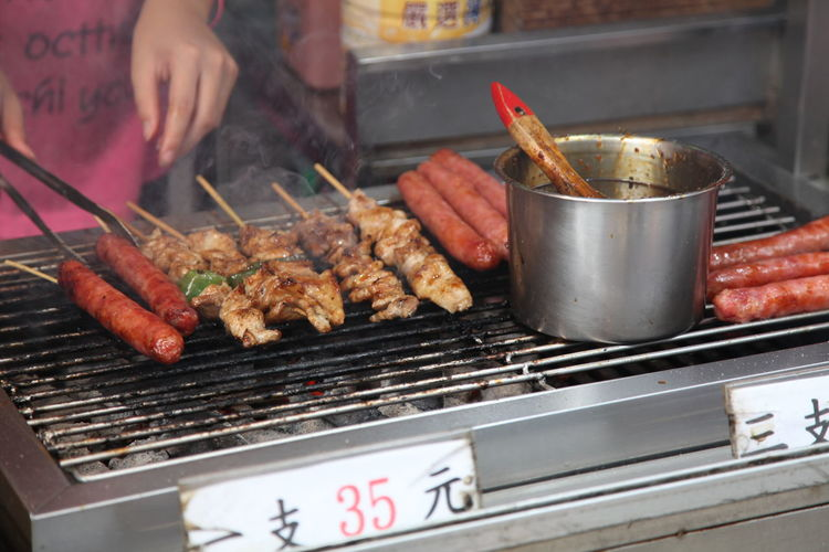 Midsection Of Person Grilling Sausages On Barbecue Grill At Market Stall