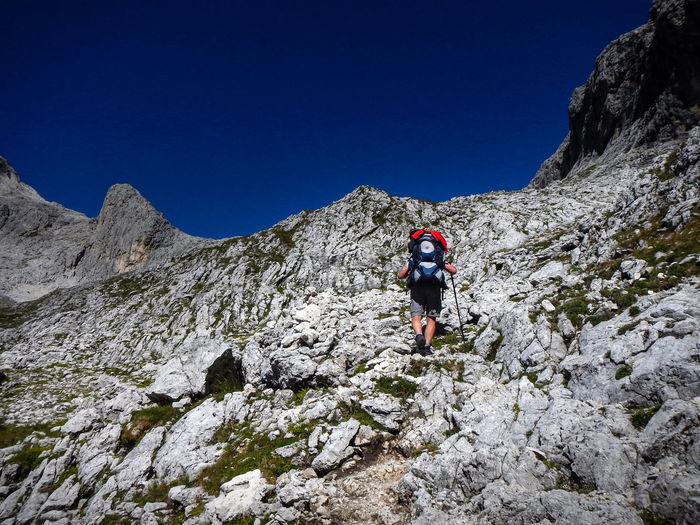 Adventure Backpack Beauty In Nature Challenge Clear Sky Cliff Climbing Day Exploration Extreme Sports Full Length Healthy Lifestyle Hiking Leisure Activity Lifestyles Low Angle View Men Mountain Nature One Person Outdoors Real People Rear View Rock - Object Rock Climbing
