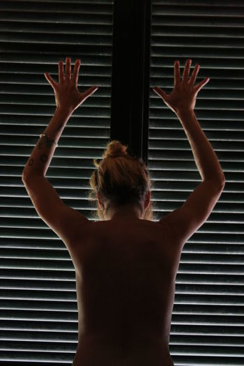 Rear view of naked woman with arms raised standing by window