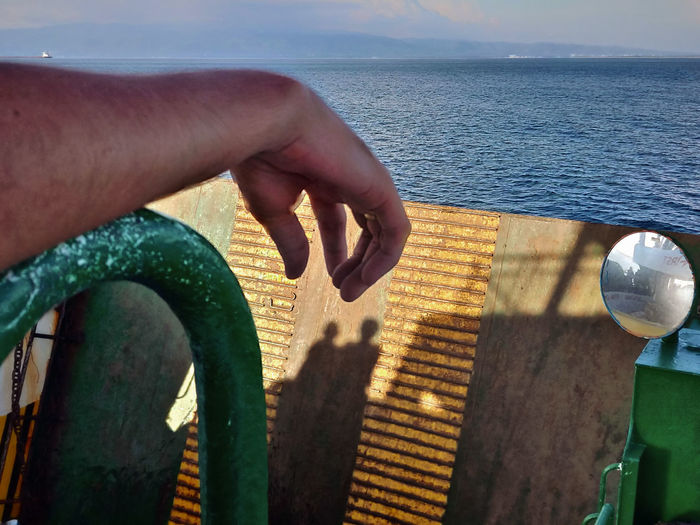 Cropped image of hand on sea shore