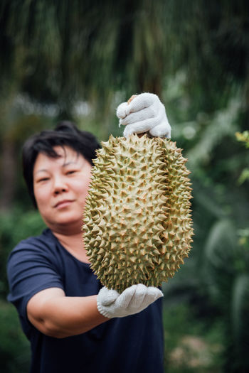 Portrait of mature woman holding durian