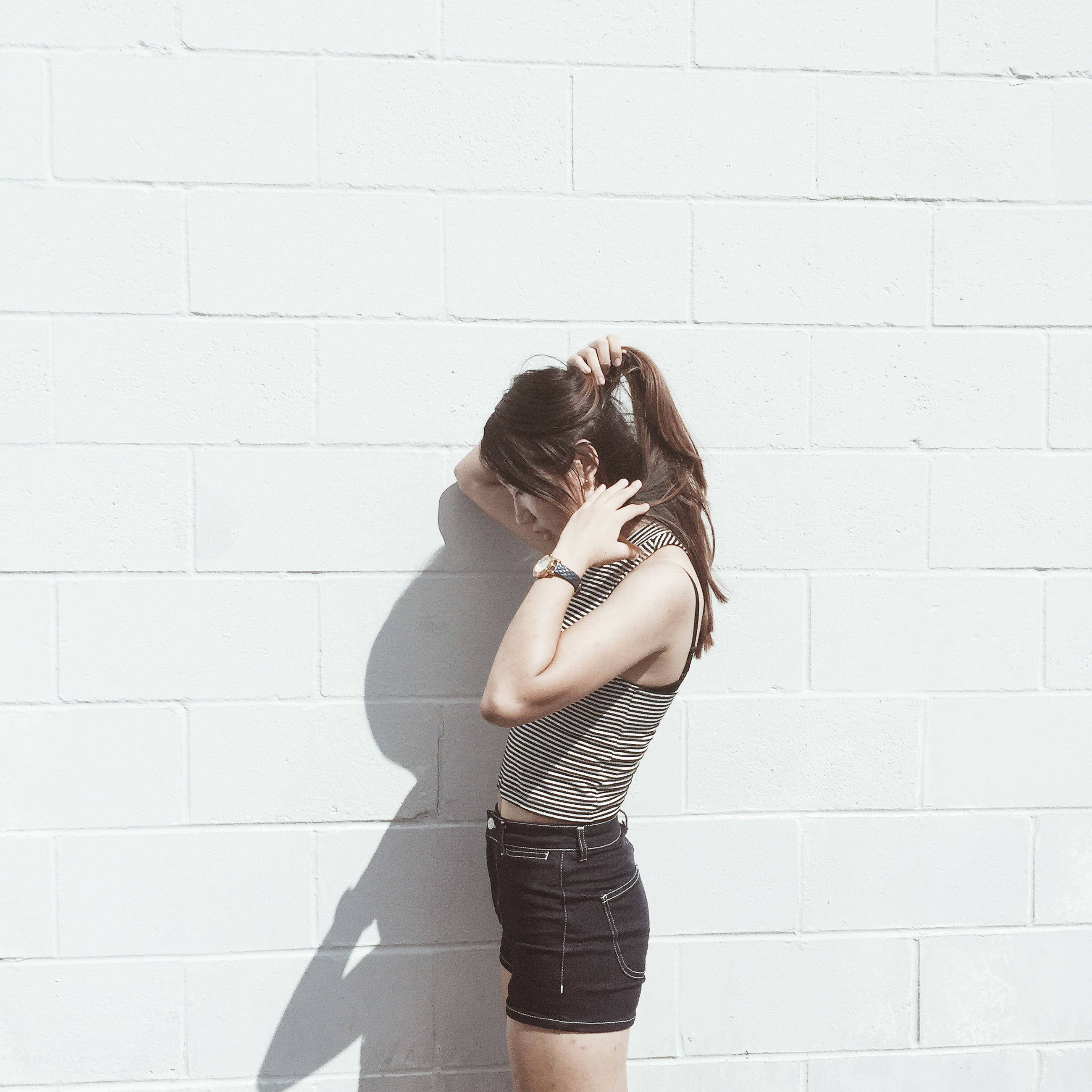 lifestyles, standing, leisure activity, person, young adult, young women, casual clothing, wall - building feature, fashion, sensuality, femininity, long hair, three quarter length, low section, front view, shadow
