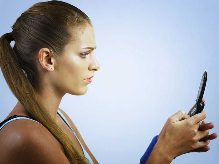 Side view of mid adult woman using phone against white background