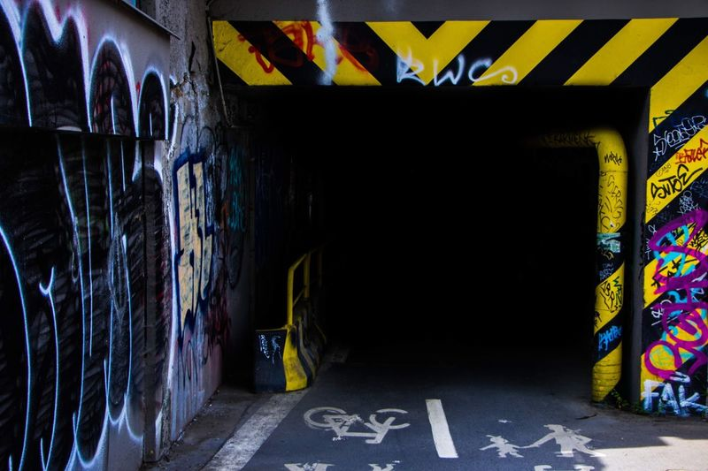 Black Graffiti Art And Craft Wall - Building Feature Creativity Architecture Street Art Communication No People Built Structure Sign Text Symbol Representation Multi Colored Western Script Outdoors City Street Direction Mural