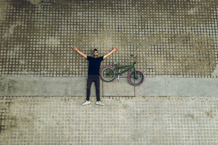 Full length of man with bicycle standing on footpath