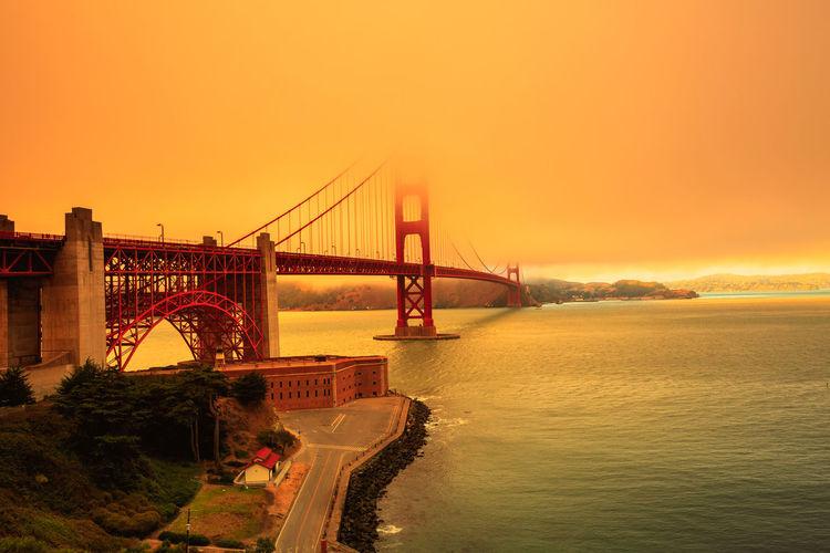 Golden gate bridge over sea against sky during sunset
