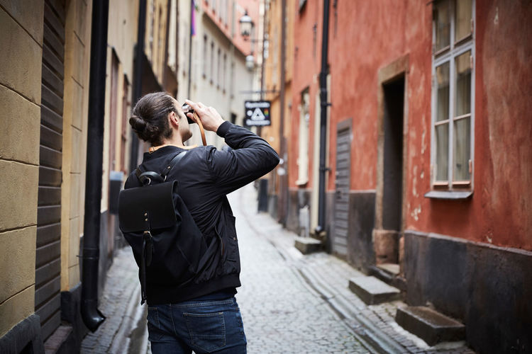 Young man photographing against buildings in city