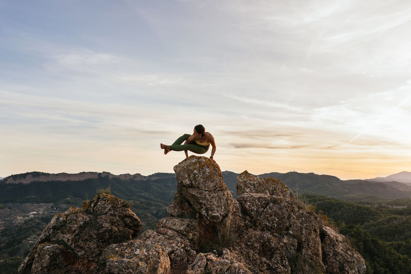 Man sitting on rock at mountain against sky