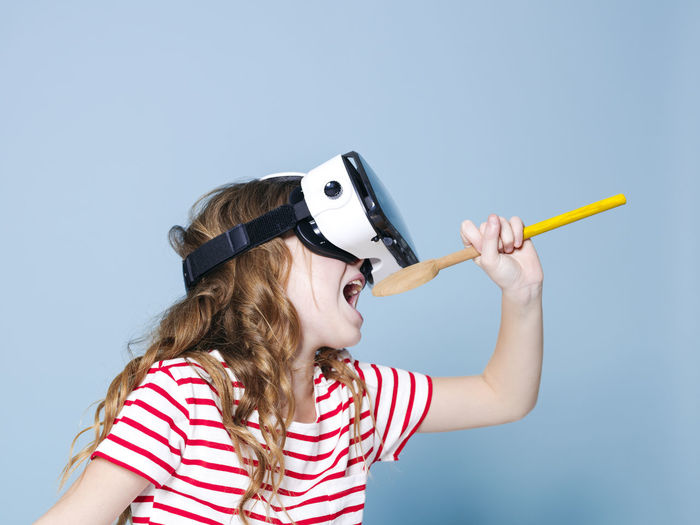 cool and smiling positive girl wearing virtual reality glasses goggles headset is singing with cooking spoon, new generation, concept in front of blue background Childhood Child Holding Women Girls Striped People Leisure Activity Females Casual Clothing Indoors  Blue Studio Shot Lifestyles Headshot Copy Space Front View Portrait 3-d Glasses Blue Background Hairstyle Eyewear 3D Virtual Cooking Spoon Goggles Girl
