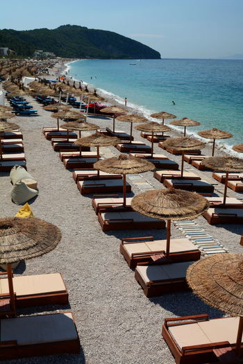 Chairs and tables on beach by sea against sky