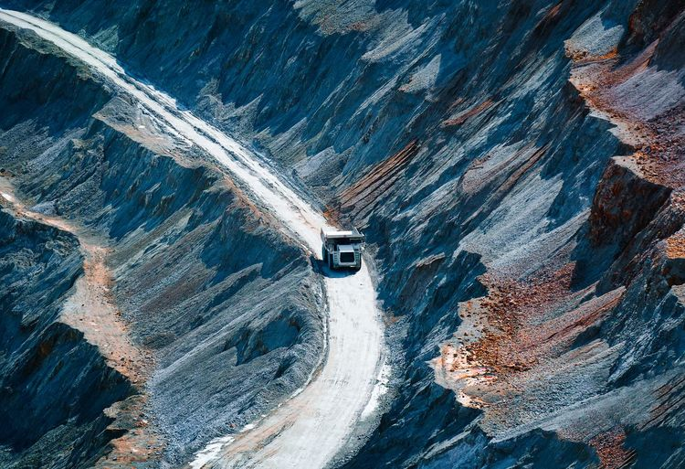 High angle view of mining vehicle road amidst rock formation in open pit mine