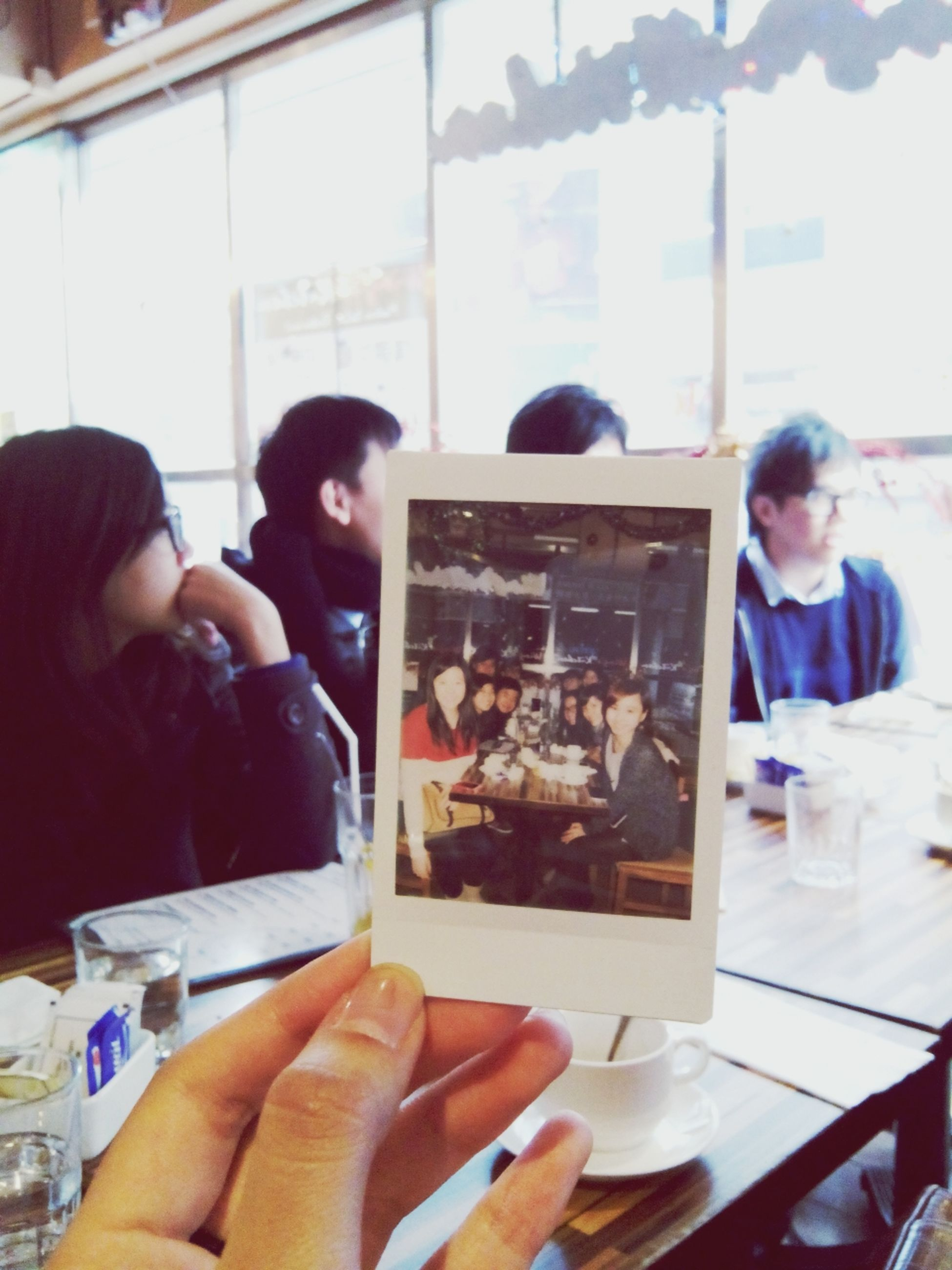 food and drink, indoors, lifestyles, leisure activity, person, sitting, casual clothing, waist up, young men, holding, food, table, young adult, restaurant, togetherness, drink, boys