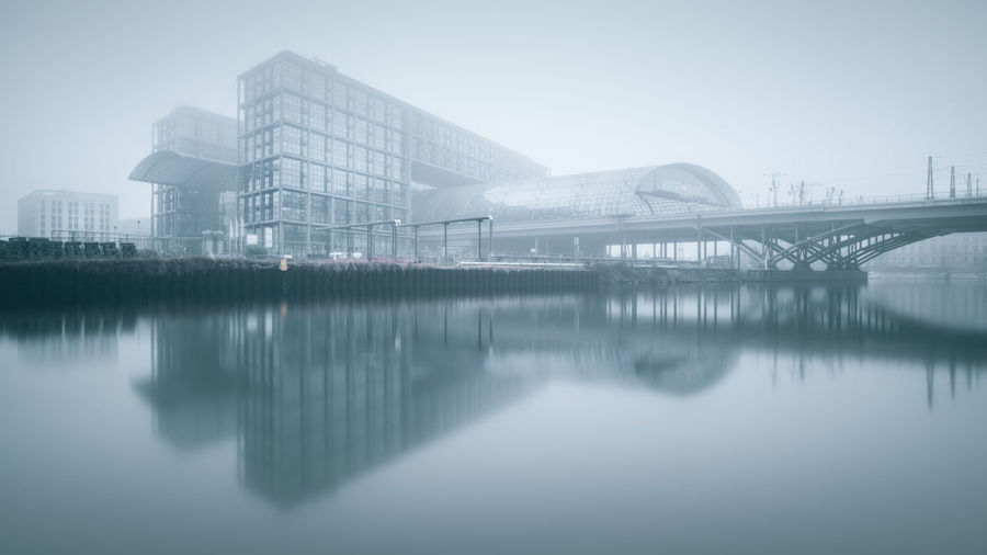 Berlin hauptbahnhof with reflection on river against sky in foggy weather