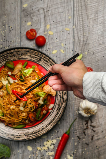Cropped hand of man holding chopsticks over food on table