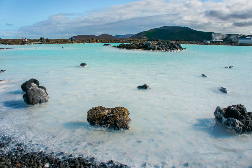 Rocks and blue water in Blue Lagoon, Iceland. Iceland Reykjavik Animal Themes Animals In The Wild Beach Beauty In Nature Blue Water Day Geothermal  Geothermal Spa Mammal Mountain Nature No People Outdoors Rock - Object Scenics Sea Sky Water