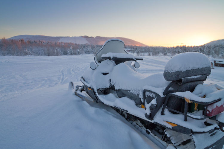 Snow covered field and snowmobile  against sky during sunset